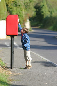 Boy posting letter in a red British post box