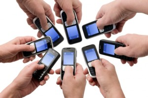 Hands holding out a collection of mobile phones
